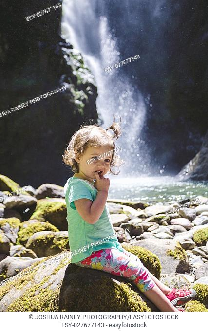 Young girl about 1. 5 years old posing for a portrait under a tall waterfall in the Umpqua National Forest in Oregon