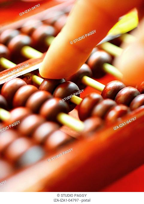 Close-up of a person's hand using a Chinese abacus