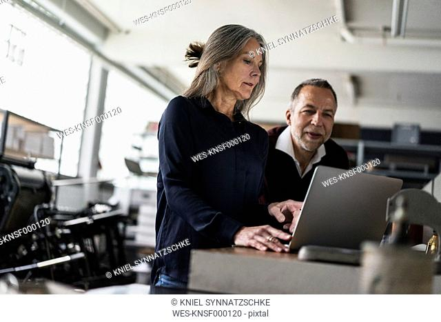 Senior woman and man in a printing shop looking at laptop