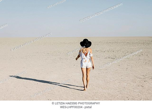 Woman with black hat, walking in the desert