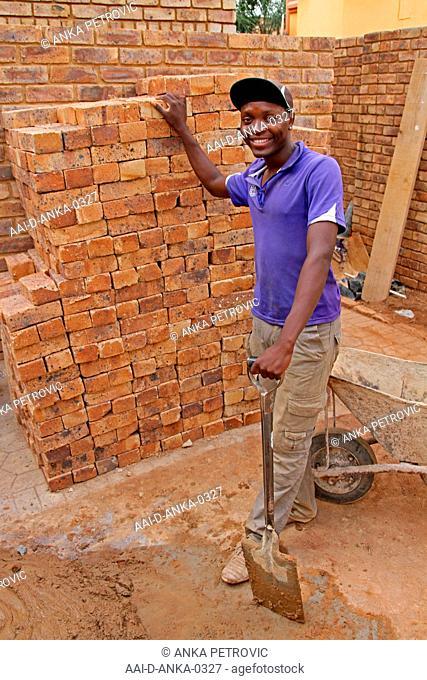 Construction worker standing next to stack of bricks, Moreleta Park, Pretoria, Gauteng Province, South Africa