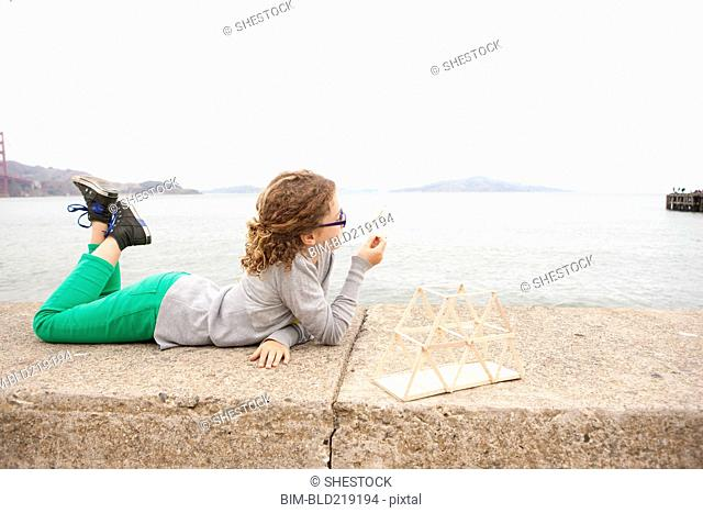 Caucasian girl examining homework project on wall over ocean