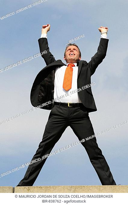 Businessman wearing a suit with a red tie, raising his arms in the air and celebrating, success, victory, delight