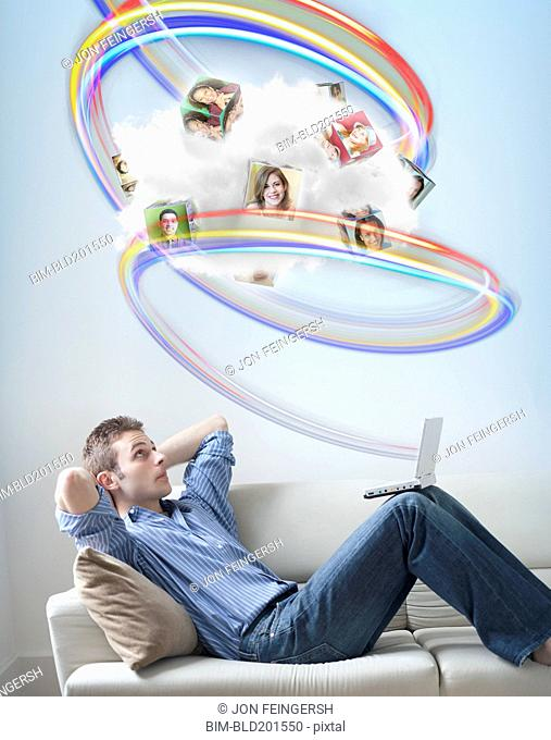 Caucasian man looking at colorful lines and images above his head