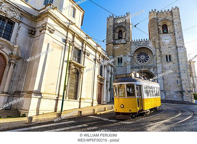 Portugal, Lisbon, typical yellow tram in front of the Cathedral