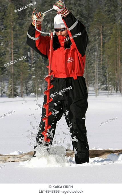 A woman is drilling a hole to do ice fishing on a lake