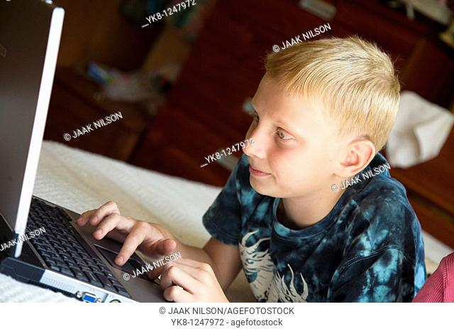 Teenage Boy Lying Down and Using Laptop Computer