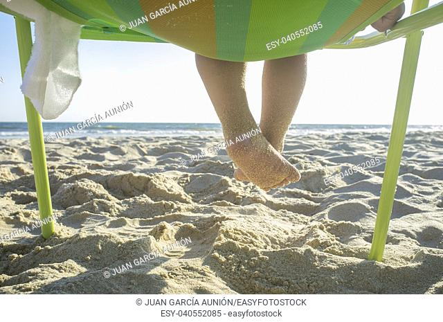 Child boy feet full of sand. He is sitting on beach chair in front of the sea