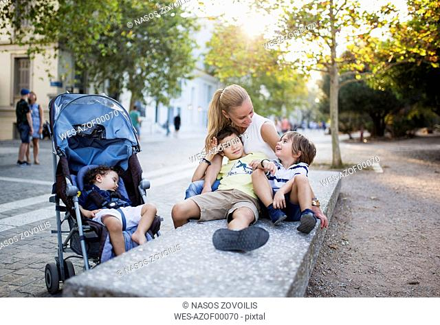 Mother sitting on bench playing with with her sons