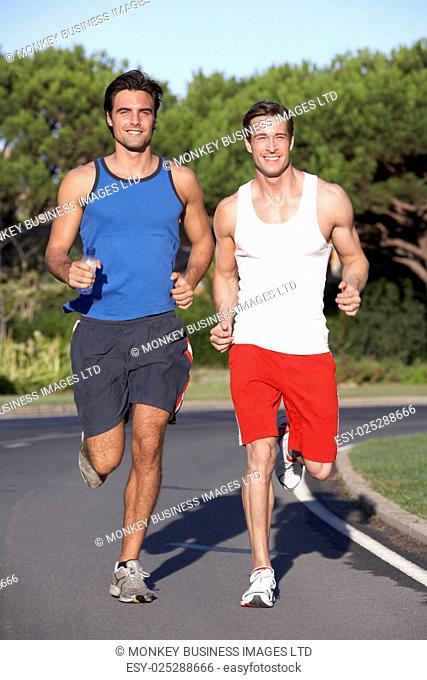 Two Men Running On Road