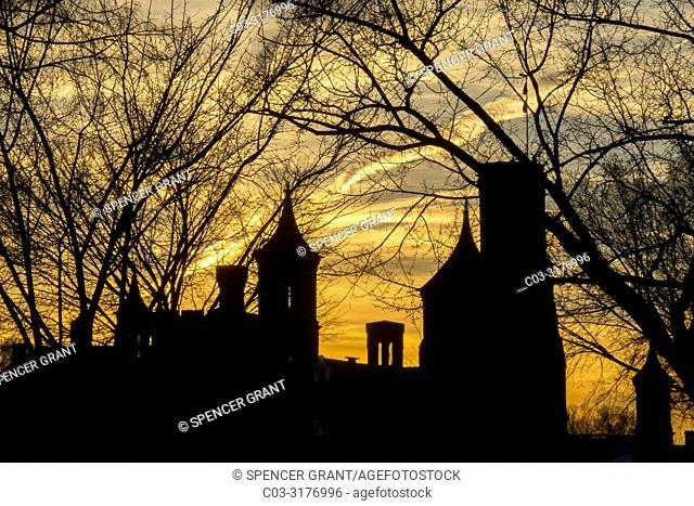 The historic 1855 Smithsonian Institution Administration Building on the National Mall in Washington, DC is silhouetted against a winter sunset and framed by...