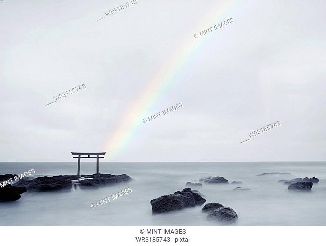 Rainbow over tall Torii gate on rocks in the middle of a lake