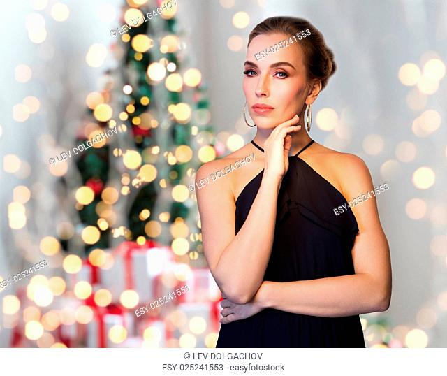 christmas, holidays, people, jewelry and luxury concept - beautiful woman in black wearing diamond earrings over lights background