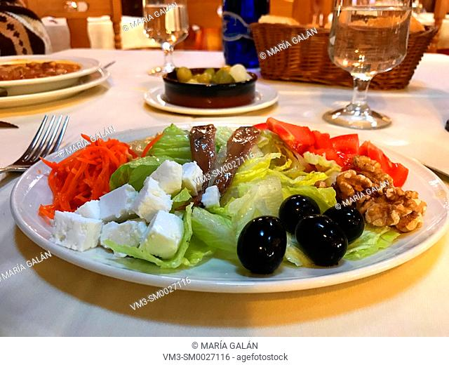 Mixed salad made of lettuce, tomato, carrot, cottage cheese, black olives, anchovy filets, nuts and olive oil