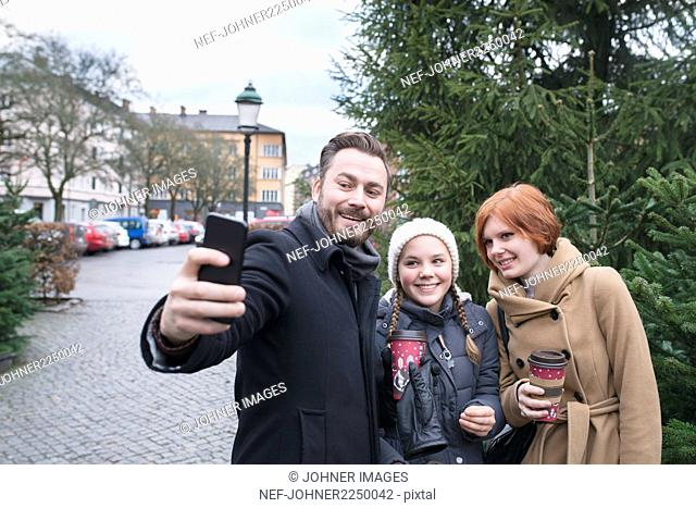 Man with teenage girls taking selfie