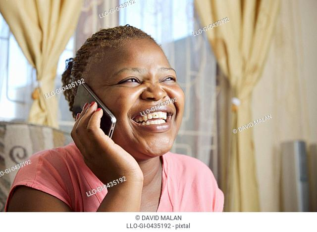Teenage girl on a mobile phone, laughing (with a gold star on her tooth). Mandalay, Cape Town, South Africa