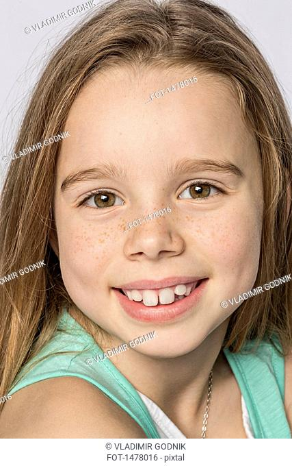 Close-up portrait of smiling cute girl against white background