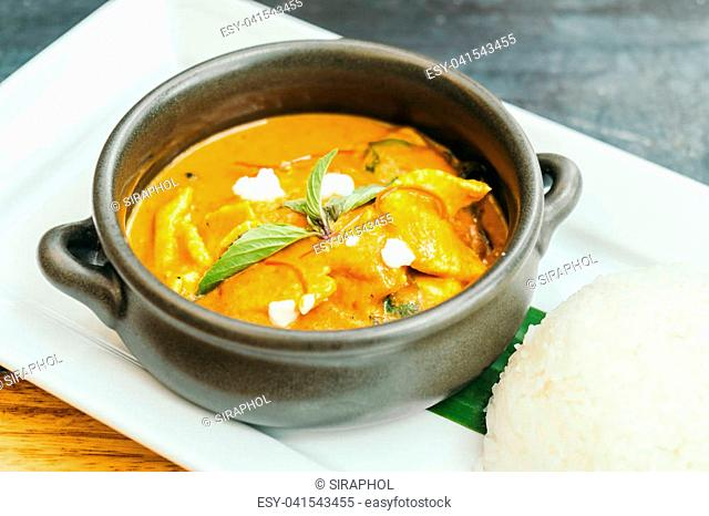 Panang curry chicken soup in black bowl with rice - Thai food style