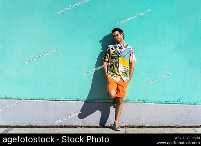 Cool man standing in front of green wall with hands in pockets