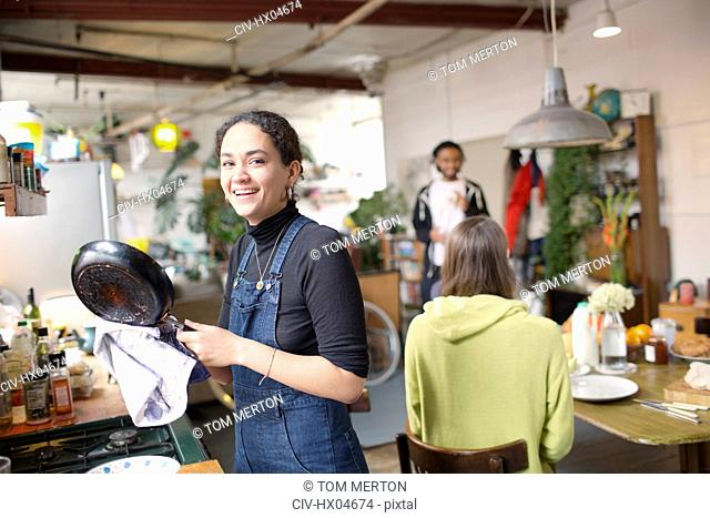 Portrait smiling young woman doing dishes in apartment