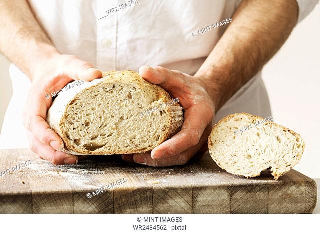 Baker holding a freshly baked loaf of bread