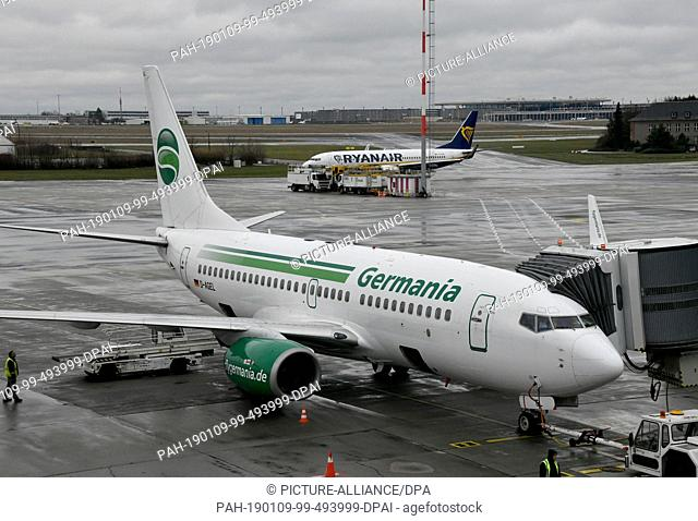 09 January 2019, Brandenburg, Schönefeld: Germania flight ST 3612 to Beirut is handled at Schoenefeld Airport, while a Ryanair aircraft rolls to take off in the...