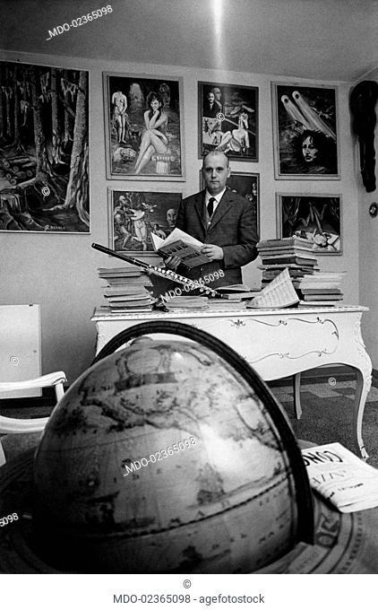 Italian professor Lando Degoli laefing through a book at his desk. Lando Degoli took part in the TV show Lascia o raddoppia in 1955. Carpi, 1965