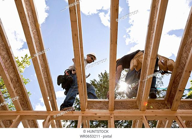 Carpenters working on second floor of a house