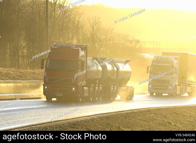 Two Volvo FH trucks, red tanker and white semi pulling freight trailer on wet road in natural, in-camera golden light. Salo, Finland. January 24, 2020