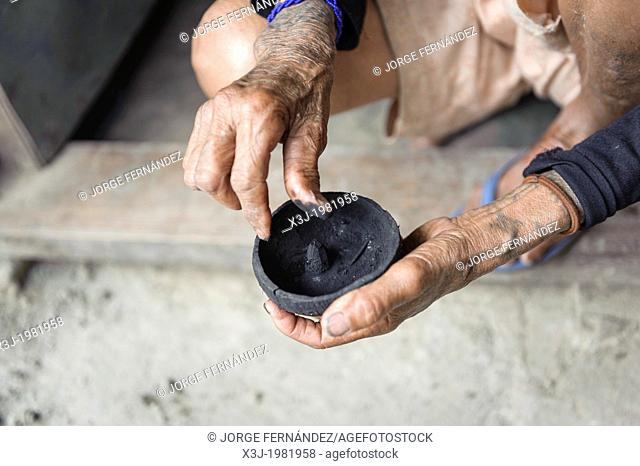 Woman preparing a mixture to make a tattoo in a traditional way, Kalinga, Philippines