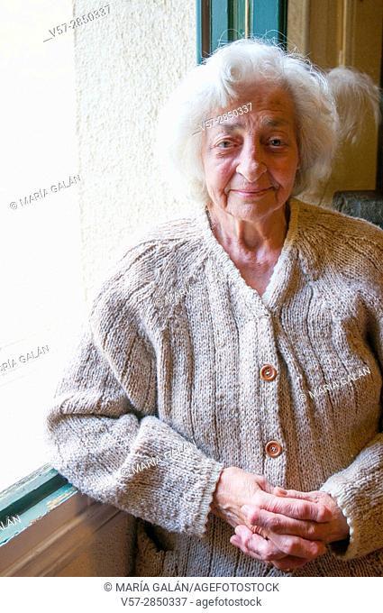 Portrait of old lady by the window, smiling and looking at the camera