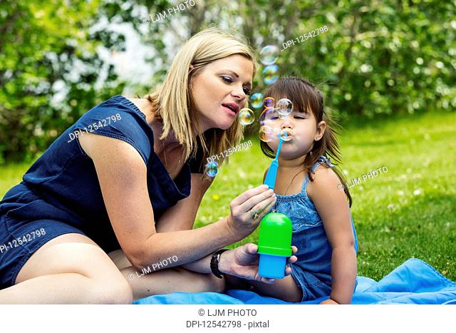 A beautiful young mother blowing bubbles with her daughter while sitting on a blanket in a city park during a warm sunny day; Edmonton, Alberta, Canada