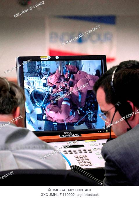 NASA managers monitor the STS-118 crew members as they board the Space Shuttle Endeavour from the Launch Control Center August 8