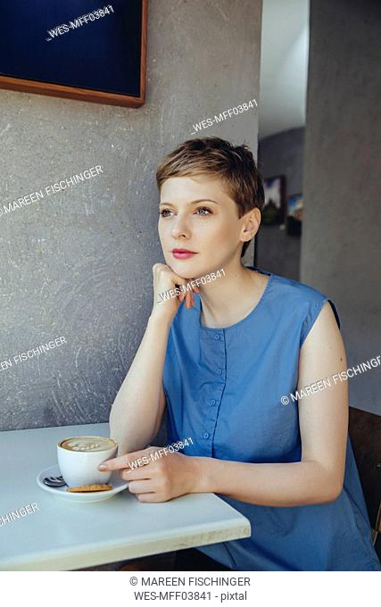 Serious woman with a cup of coffee in a cafe