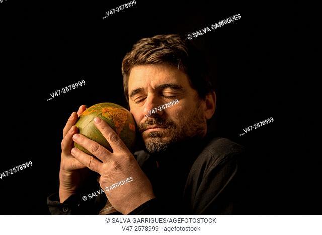 Man embracing the globe with the eye closed, black studio photo sobrefondo
