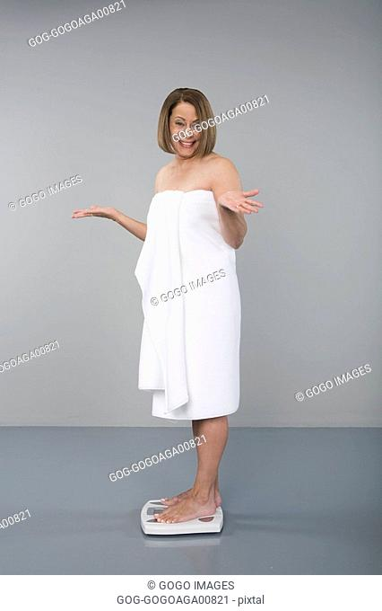 Woman in towel standing on scale