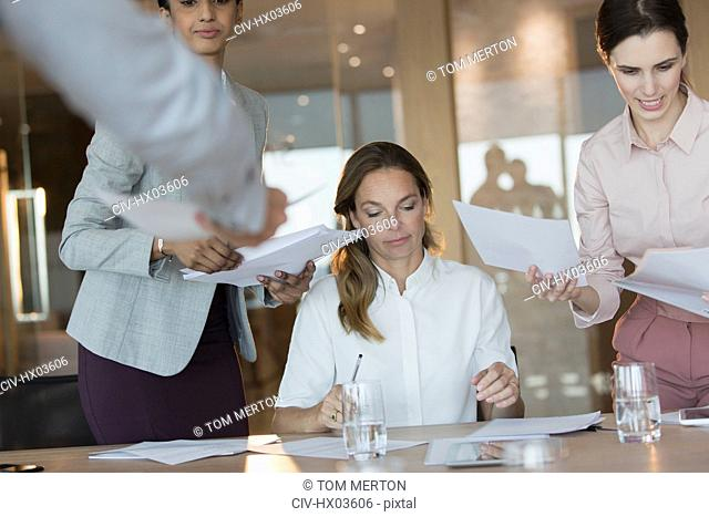 Business people signing and reviewing paperwork in conference room meeting