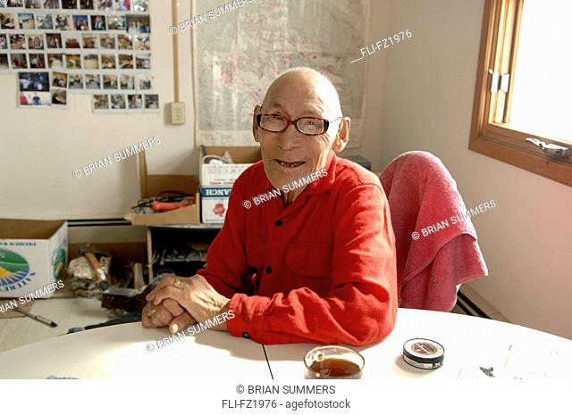 Elder sitting at kitchen table, Cambridge Bay, Nunavut