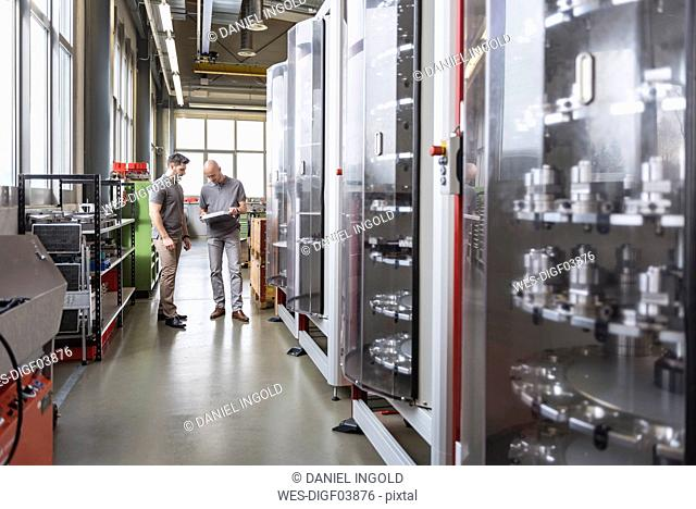 Two men examining product in modern factory