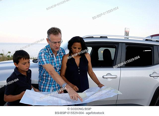Vacationing family looking at a map