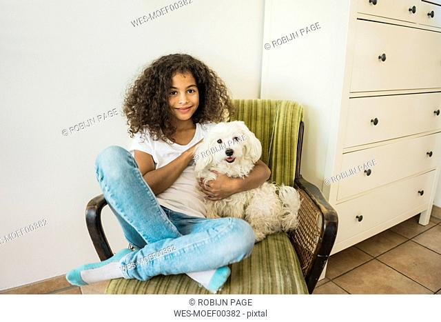 Animal loving little girl sitting in armchair petting her white dog
