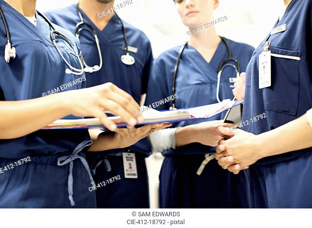 Team of doctors with stethoscopes looking at documents in hospital