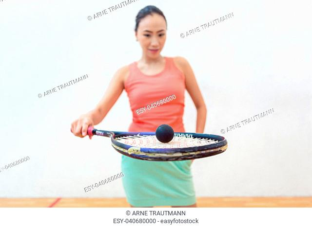 Close-up of a rubber hollow ball on the new squash racket of a fit Chinese woman standing against white wall