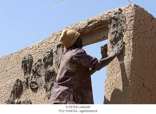 Man applying mud to a house, Djenne, Mali