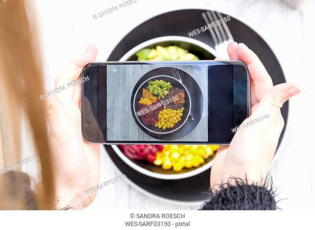 Girl taking a photo of lunch bowl with her smartphone, close-up
