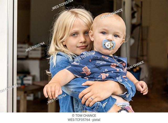 Portrait of girl holding baby boy brother at home