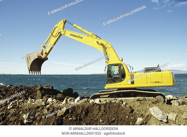 A construction site, ocean in the background and a clear blue sky
