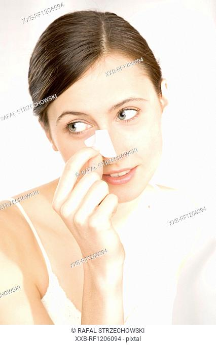 woman taking off cleansing strip