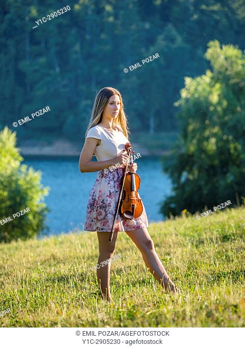 Young female violinist in nature near lake. Croatia