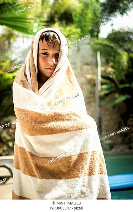 A boy standing wrapped in a towel and smiling into shot